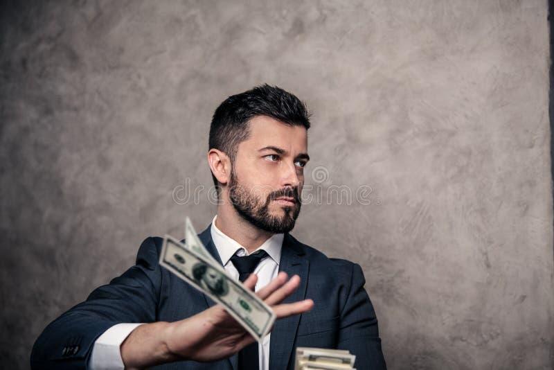 Portret van een jonge knappe zakenman die geldbankbiljetten weggooien het dragen van kostuum en een band stock afbeeldingen