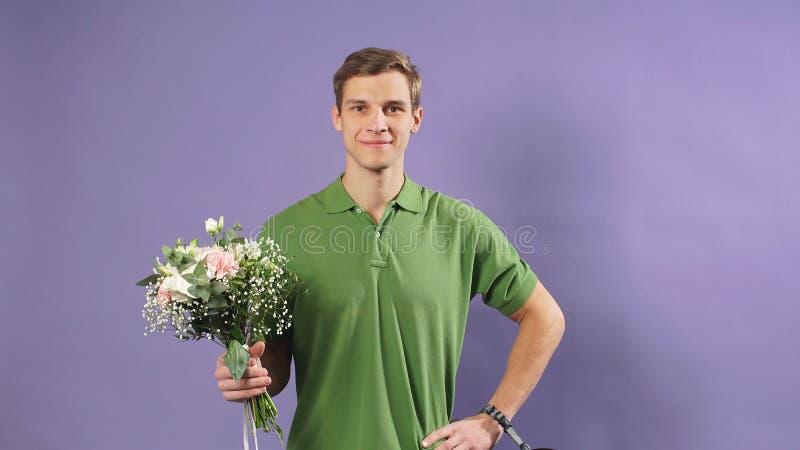 Portret van een jonge koerier met bloemen in zijn handen op een geïsoleerde achtergrond, Express-bezorgingsservice royalty-vrije stock fotografie