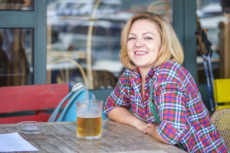 Portret van een jonge leuke het glimlachen meisjeszitting in een koffie met een mok bier stock foto's