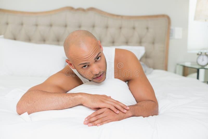 Portret van een jonge mens die in bed rusten stock afbeelding