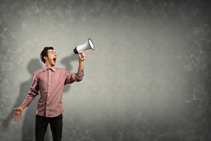 Portret van een jonge mens die gebruikend megafoon schreeuwen stock afbeeldingen
