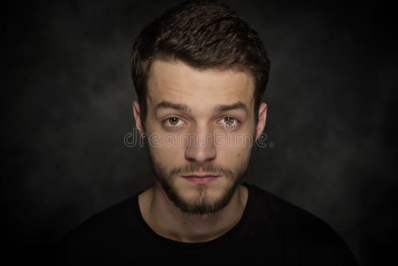 Portret van een jonge mens met een baard op een donkere achtergrond royalty-vrije stock fotografie