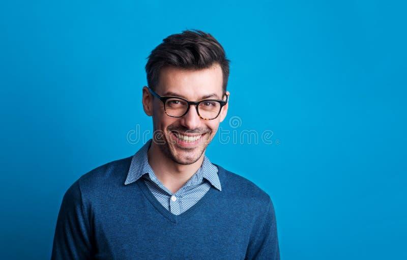 Portret van een jonge mens met glazen in een studio op een blauwe achtergrond stock foto