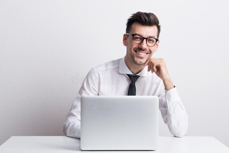 Portret van een jonge mens met laptop in een studio, het werken royalty-vrije stock afbeelding