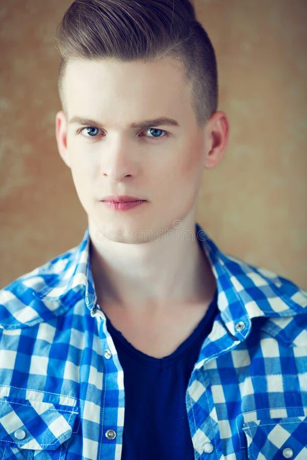 Portret van een jonge mens met zeer knap gezicht in blauw toevallig s stock foto's