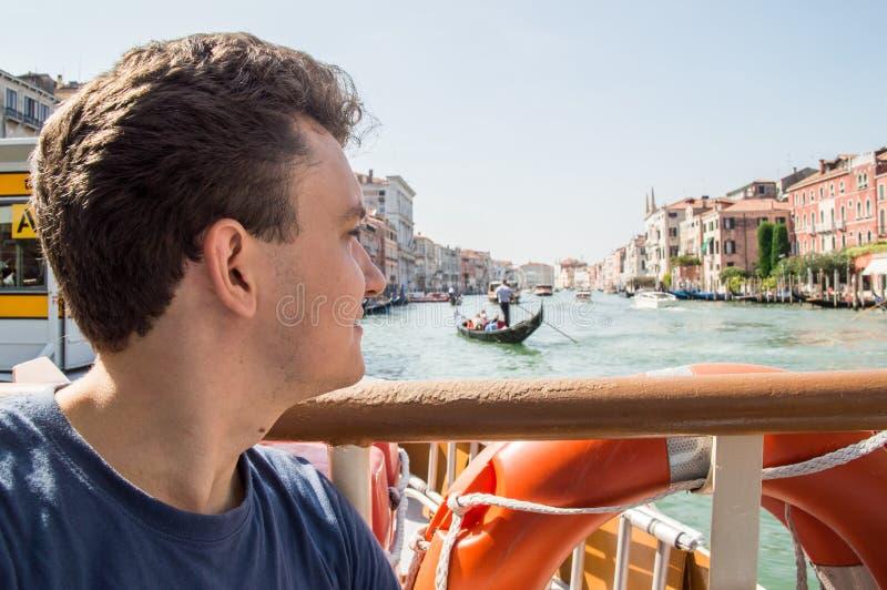 Portret van een jonge mens op een Grand Canal -cruise op de boog van een riviertram De blik wordt geleid aan de horizon royalty-vrije stock afbeeldingen