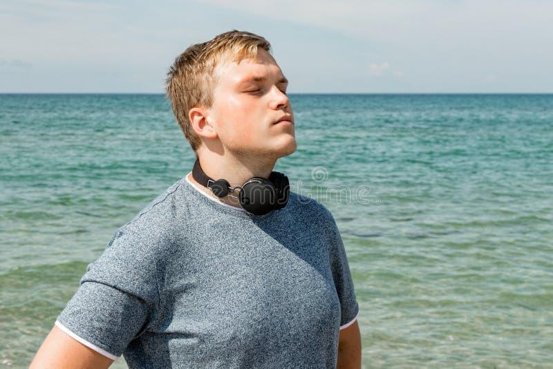Portret van een jonge mens op het strand die aan muziek op hoofdtelefoons luisteren De reis en ontspant royalty-vrije stock foto