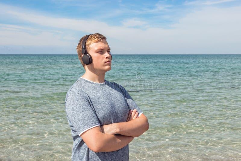 Portret van een jonge mens op het strand die aan muziek op hoofdtelefoons luisteren De reis en ontspant stock foto's