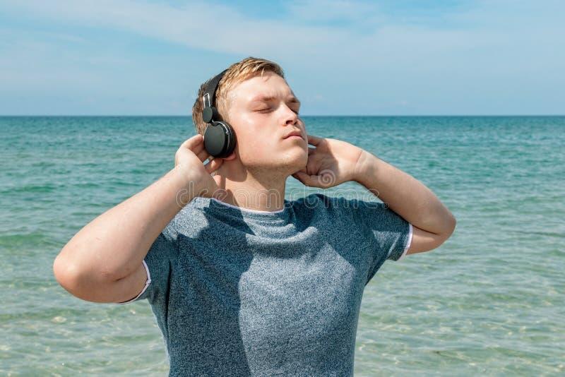 Portret van een jonge mens op het strand die aan muziek op hoofdtelefoons luisteren De reis en ontspant royalty-vrije stock afbeelding