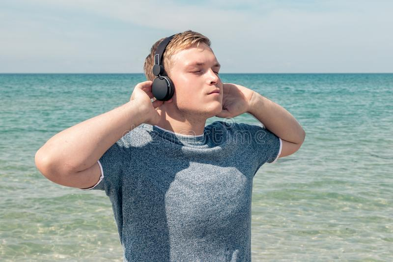 Portret van een jonge mens op het strand die aan muziek op hoofdtelefoons luisteren De reis en ontspant stock afbeelding