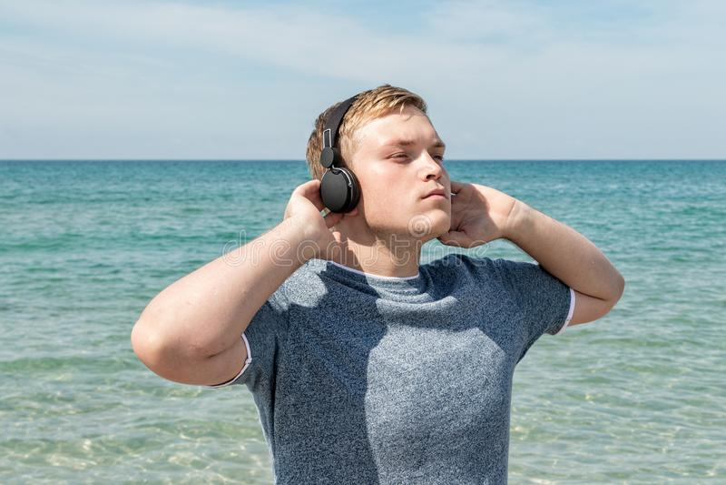 Portret van een jonge mens op het strand die aan muziek op hoofdtelefoons luisteren De reis en ontspant stock afbeeldingen