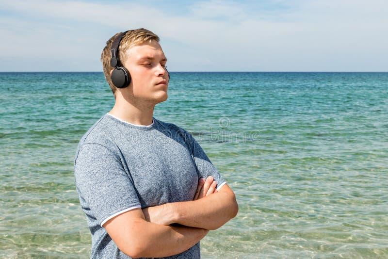 Portret van een jonge mens op het strand die aan muziek op hoofdtelefoons luisteren De reis en ontspant royalty-vrije stock fotografie