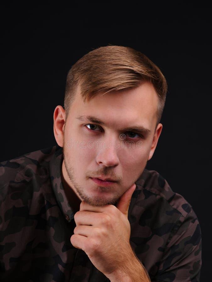 Portret van een jonge mens op een zwarte achtergrond stock fotografie