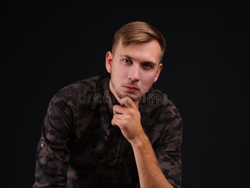 Portret van een jonge mens op een zwarte achtergrond royalty-vrije stock foto's