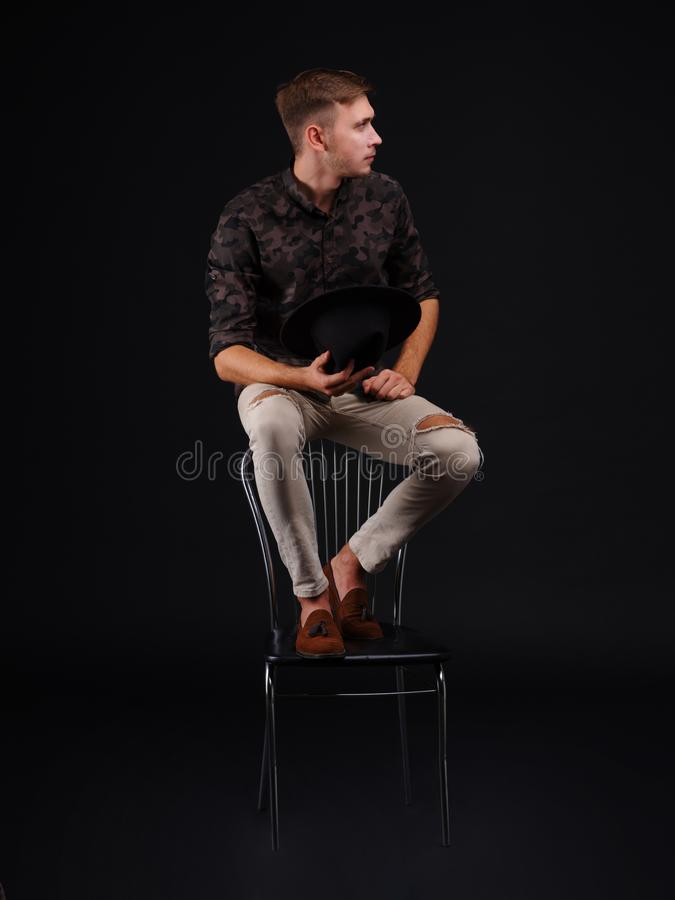 Portret van een jonge mensenzitting op een stoel in een volledige post, royalty-vrije stock foto's