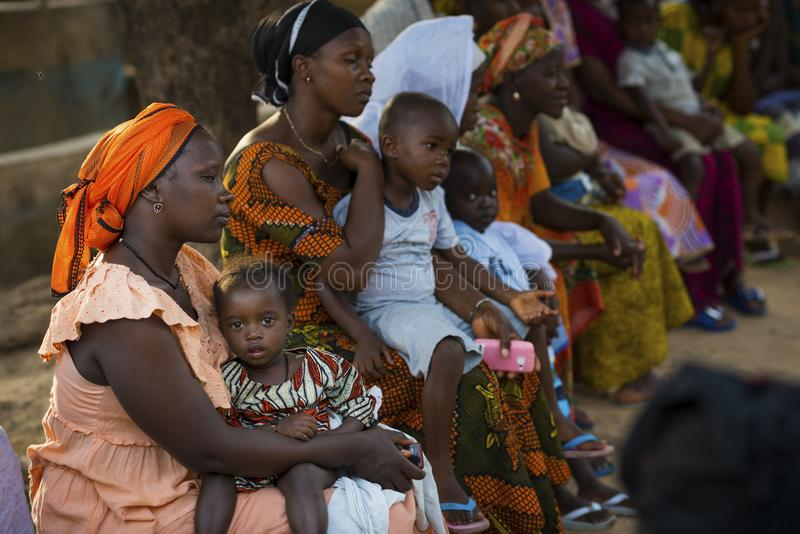 Portret van een jonge moeder en haar babydochter tijdens een communautaire vergadering, bij de Bissaque-buurt in de stad van Biss royalty-vrije stock afbeelding