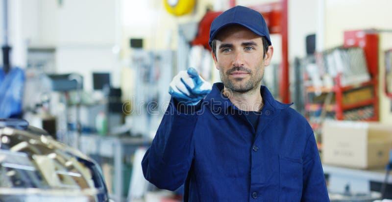 Portret van een jonge mooie autowerktuigkundige in een autoworkshop, op de achtergrond van een het Conceptenreparatie van de auto royalty-vrije stock afbeeldingen