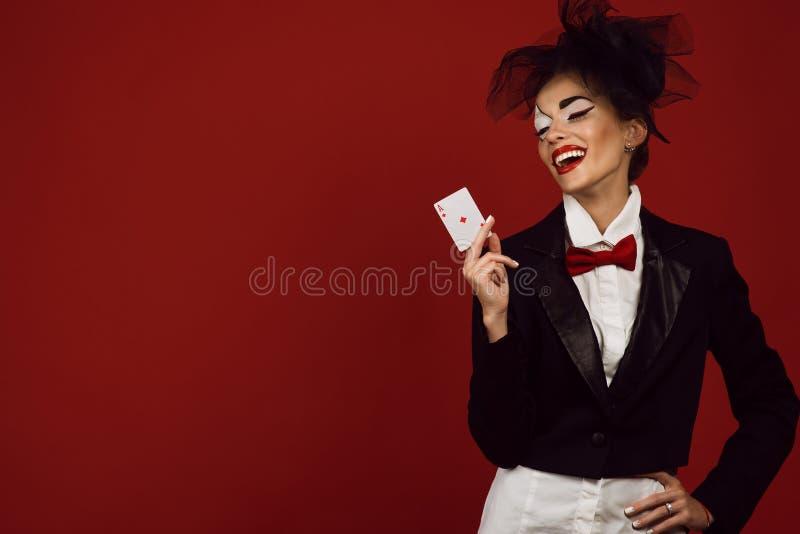 Portret van een jonge mooie damecroupier in een beeld die van joker een aas kaart en het lachen houden stock afbeeldingen