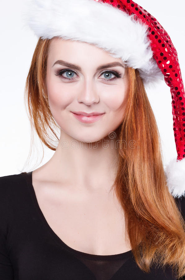 Portret van een jonge mooie roodharige vrouw in een glanzende Kerstmishoed, speelt zij met een pluizige witte pompom stock afbeeldingen