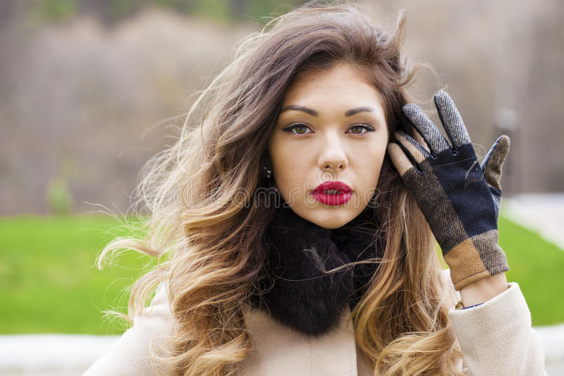 Portret van een jonge mooie vrouw in beige laag royalty-vrije stock foto
