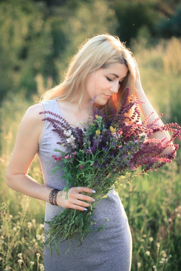 Portret van een jonge mooie vrouw in de aard met een boeket van bloemen stock fotografie