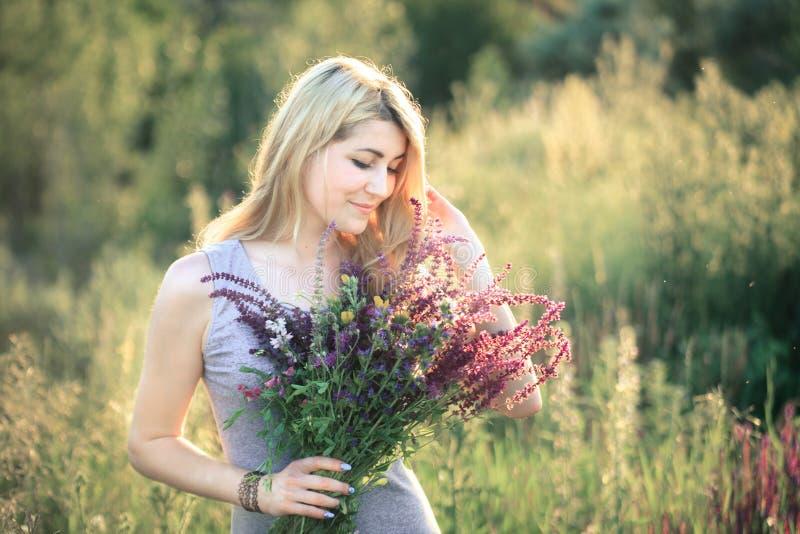 Portret van een jonge mooie vrouw in de aard met een boeket van bloemen royalty-vrije stock foto