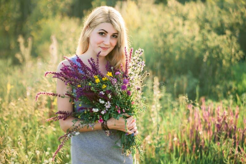 Portret van een jonge mooie vrouw in de aard met een boeket van bloemen royalty-vrije stock foto's