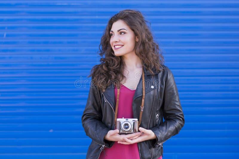 Portret van een jonge mooie vrouw die een uitstekende camera houden ove stock afbeelding