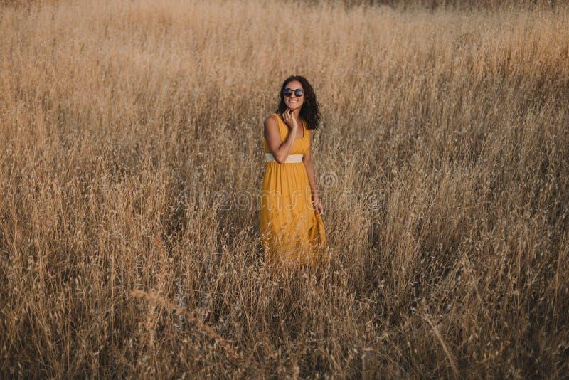 portret van een Jonge mooie vrouw die in gele kleding de camera en het glimlachen bekijken Platteland outdoors reis concept stock afbeeldingen