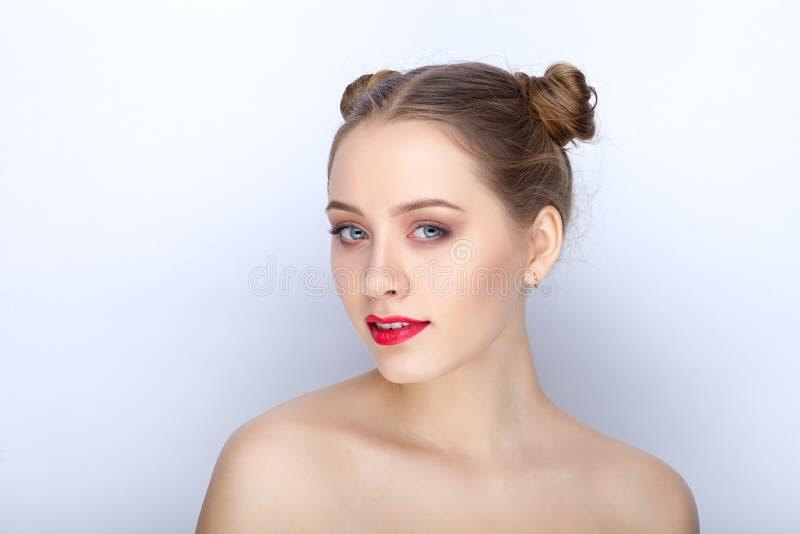 Portret van een jonge mooie vrouw met grappig het broodjeskapsel van in make-up helder rood lippen en naakte schoudershandeling d royalty-vrije stock afbeeldingen