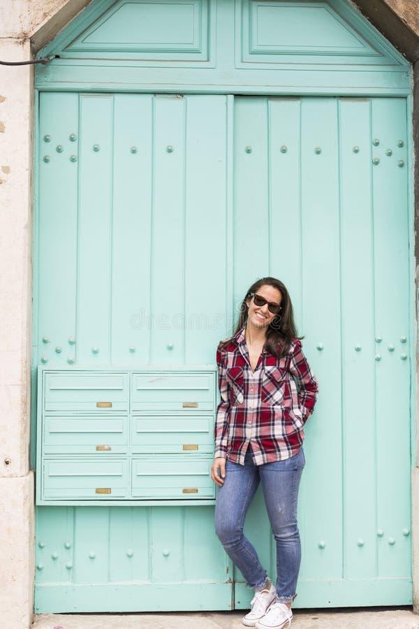 Portret van een jonge mooie vrouw over een turkooise blauwe deur B stock foto