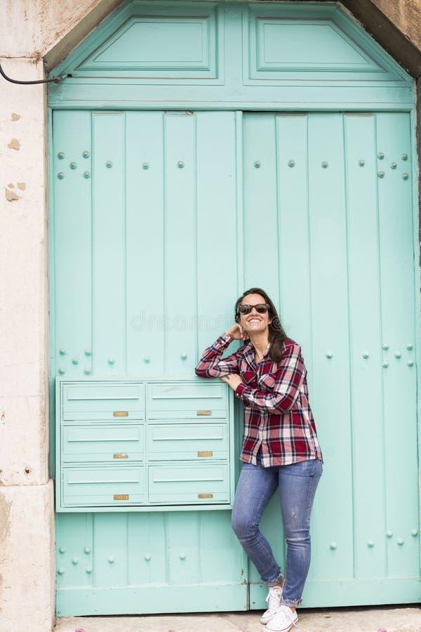 Portret van een jonge mooie vrouw over een turkooise blauwe deur B royalty-vrije stock afbeelding
