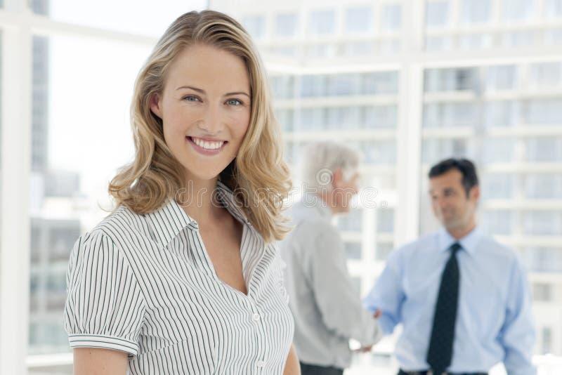 Portret van een jonge onderneemster met partners op achtergrond stock afbeelding