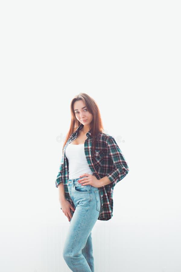 Portret van een jonge slender-brunette-vrouw in onregelmatige kleding die zich op een witte achtergrond vormt Achter de gloed Ver stock afbeelding