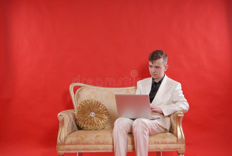 Portret van een jonge tienermens die wit bureaukostuum dragen en op de gouden luxebank zitten op rode achtergrond hij werkt aan L royalty-vrije stock afbeeldingen