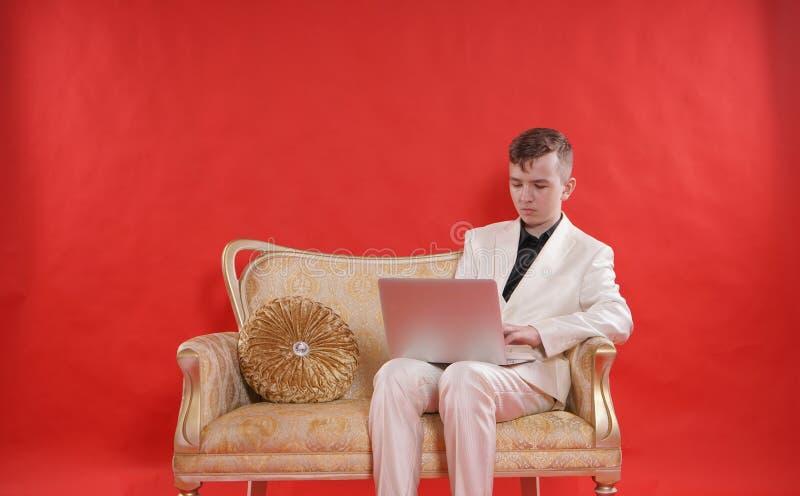 Portret van een jonge tienermens die wit bureaukostuum dragen en op de gouden luxebank zitten op rode achtergrond hij werkt aan L stock foto's