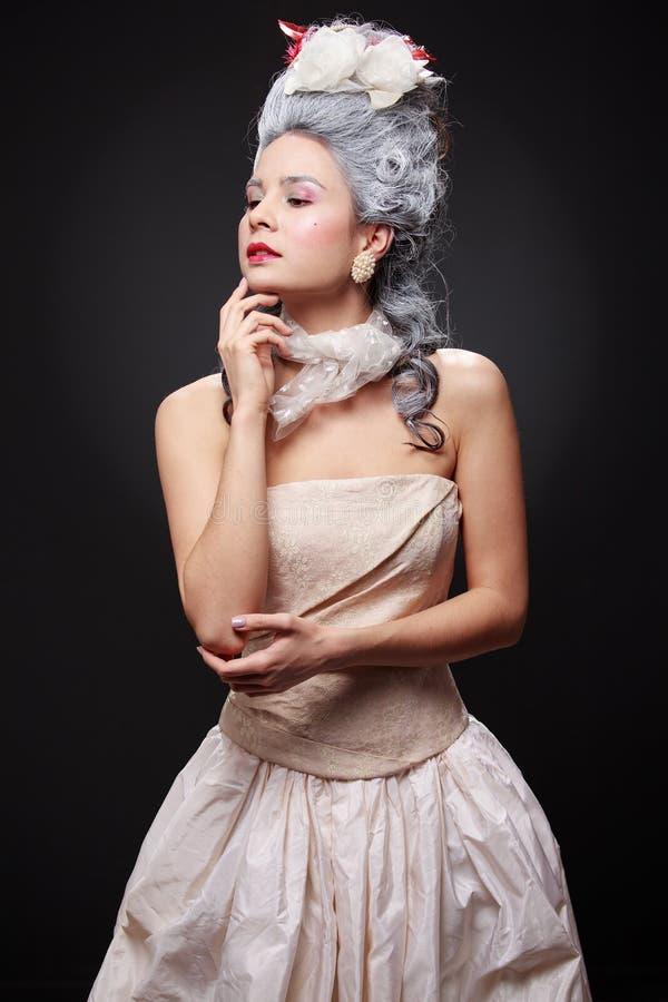 Portret van een jonge verwaande vrouw in een rococo'sstijl stock foto