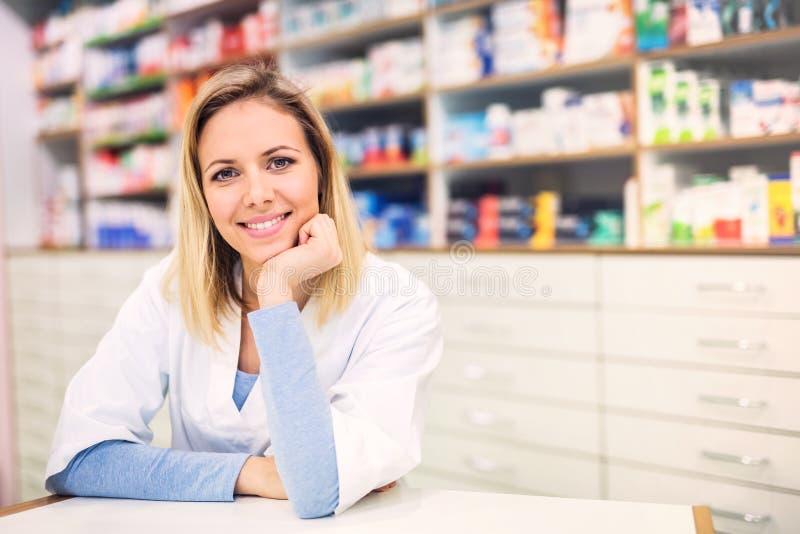Portret van een jonge vriendschappelijke vrouwelijke apotheker stock afbeelding