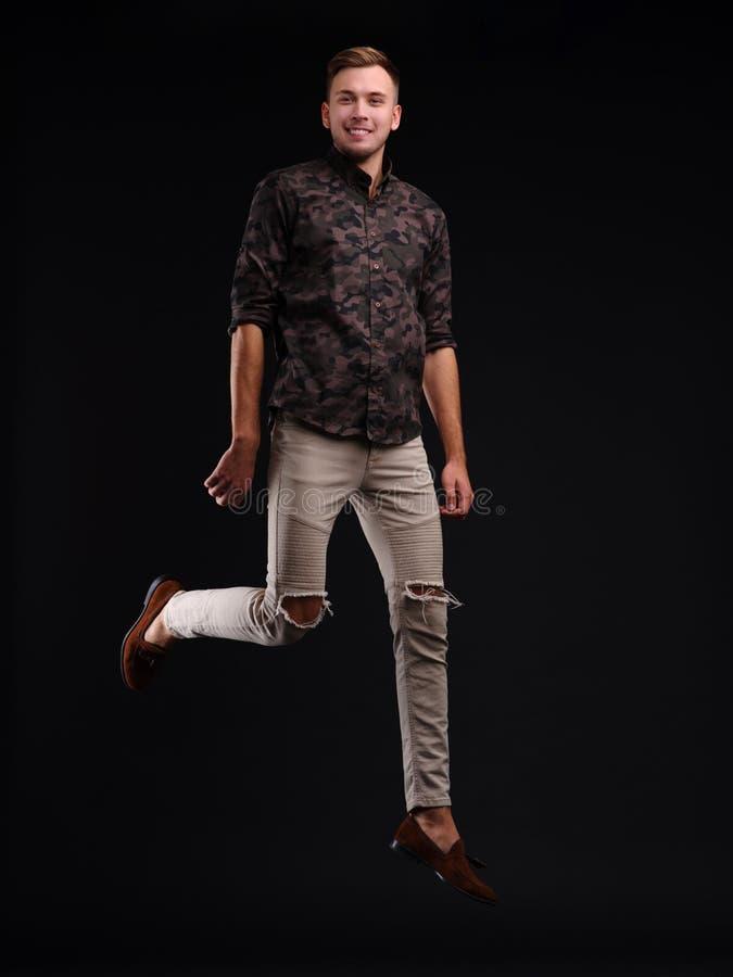 Portret van een jonge vrolijke mens in lucht het stellen tegen een zwarte achtergrond stock foto