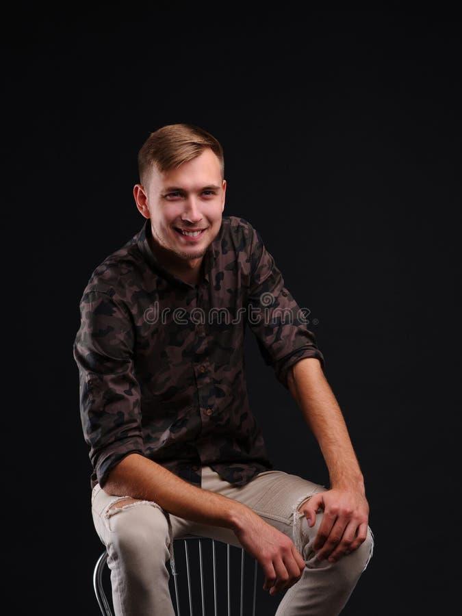 Portret van een jonge vrolijke mens op een zwarte zitting als achtergrond op een stoel royalty-vrije stock afbeelding