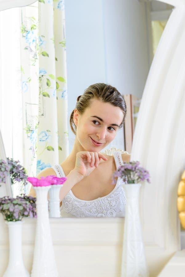Portret van een jonge vrouw bij de spiegel stock foto's