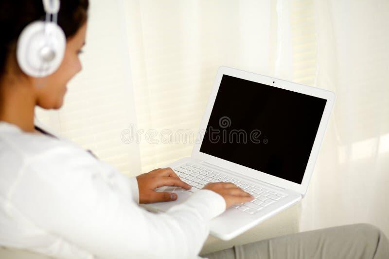 Jonge vrouw die aan laptop het luisteren muziek werkt royalty-vrije stock foto