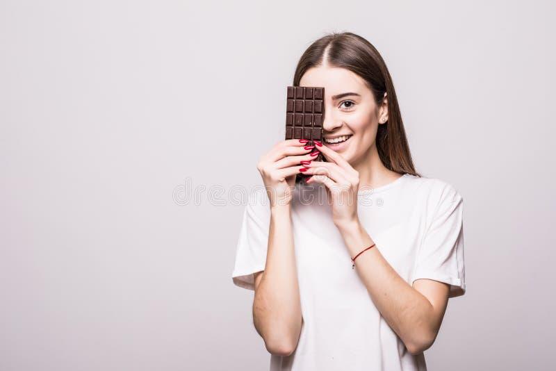 Portret van een jonge vrouw die een chocoladereep eten tegen een grijze achtergrond Het concept van de gezondheid royalty-vrije stock foto