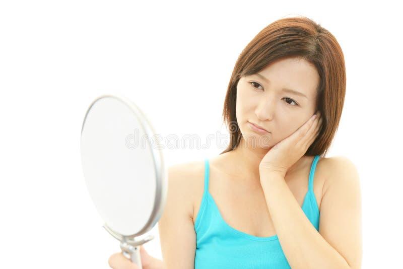 Portret van een jonge vrouw die gedeprimeerd kijken stock afbeelding