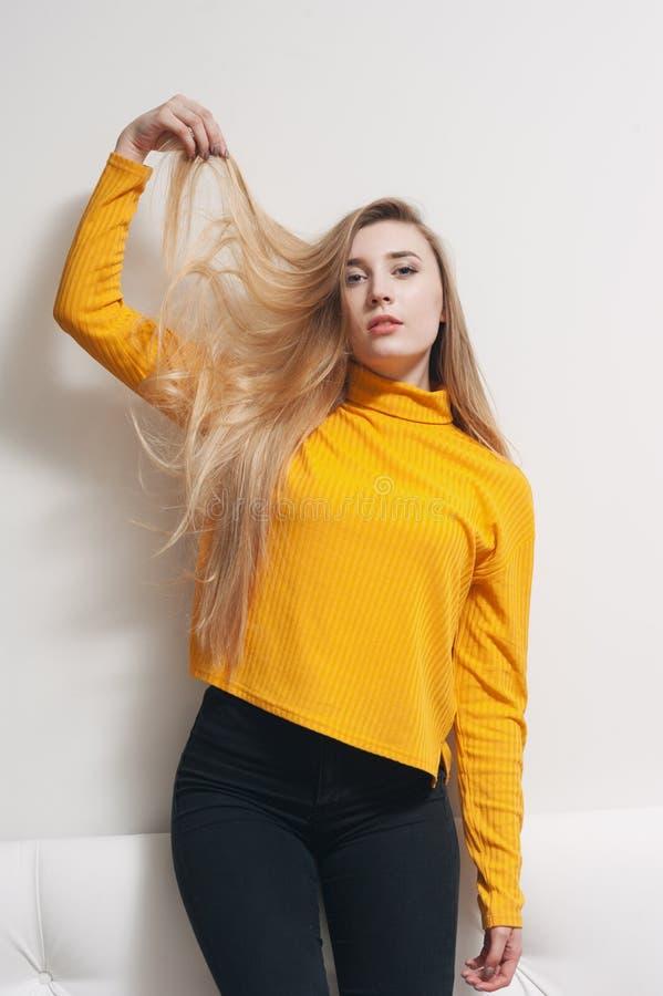 Portret van een jonge vrouw die haar haar met gescheiden droge einden houden die zich op een lichtgrijze achtergrond bevinden royalty-vrije stock fotografie