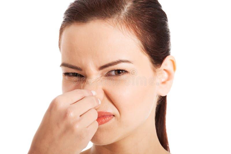 Portret van een jonge vrouw die haar neus houden. stock afbeelding