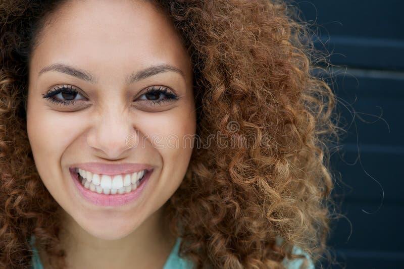 Portret van een jonge vrouw die met gelukkige uitdrukking op gezicht glimlachen royalty-vrije stock afbeelding