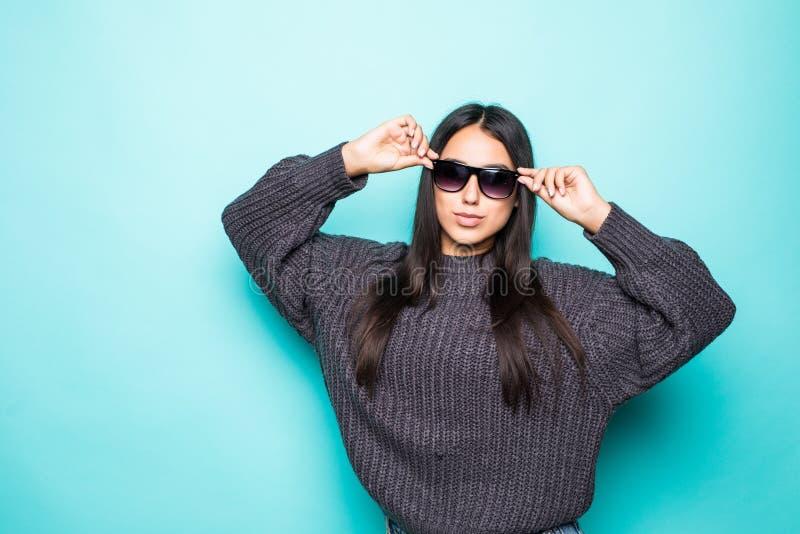 Portret van een jonge vrouw die in die sweater in zonnebril weg exemplaarruimte bekijken over blauwe achtergrond wordt geïsoleerd stock foto