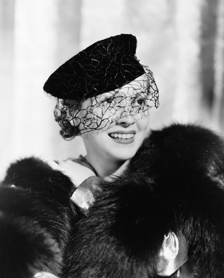 Portret van een jonge vrouw in een hoed met een sluier en bontstole het glimlachen (Alle afgeschilderde personen leven niet lange stock foto