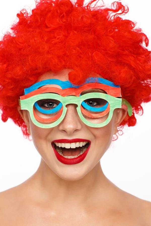 Portret van een jonge vrouw in het beeld van een clown met een rode pruik op haar hoofd stock foto